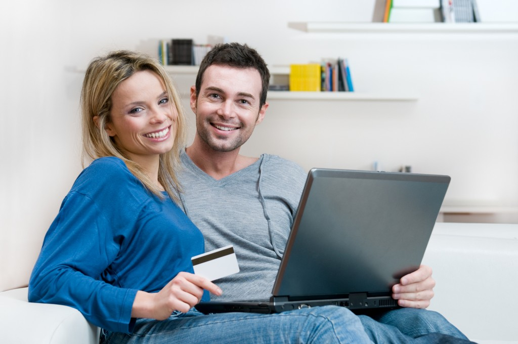 Smiling young couple making shopping online with credit card and
